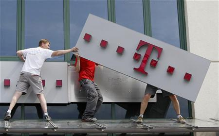 Workers redecorate a former Era Mobile phone outlet with T-Mobile logo in Warsaw
