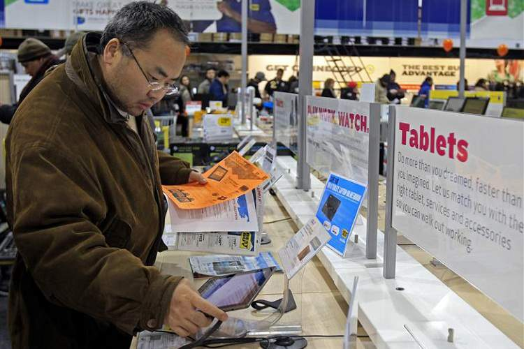 """A shopper looks at tablet computers at a Best Buy Store on the shopping day dubbed """"Black Friday"""" in Framingham"""